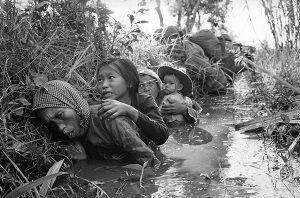 Vietnam War Family huddled in ditch