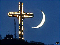 Illuminated Cross with Crescent Moon in sky