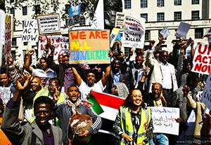 London Rally for Sudan with sign: we are all elbow lickers
