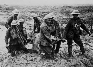 Soldiers carry wounded in a field in WW1