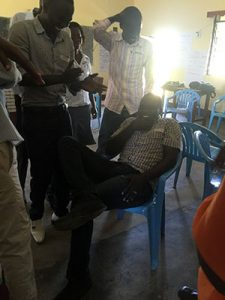 Young man sits in a chair during on of the exercises