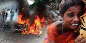 Woman cries while a fire burns in background